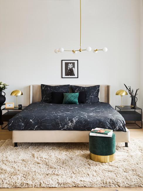 beige bed met zwarte lakens en donkere poef
