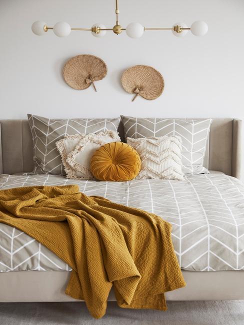 beige bed met grijs dekbed en geel kleed