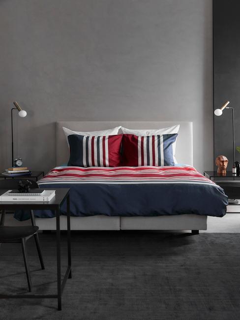 grijs bed met rood, wit, blauw dekbed