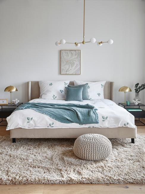 beige bed met wit dekbed en beige poef