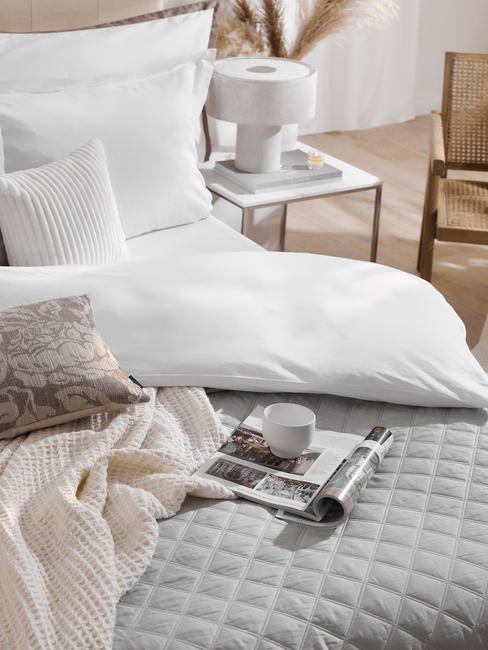 grijze deken op wit dekbed met tijdschrift