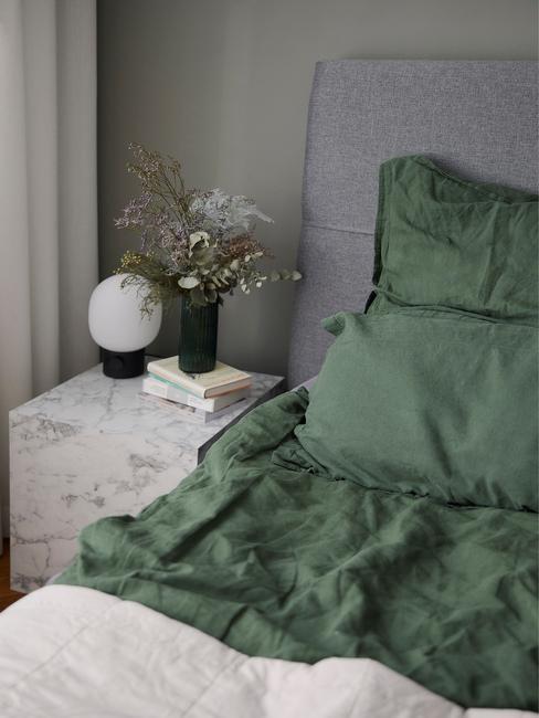 grijs bed met groen dekbed en marmere tafel