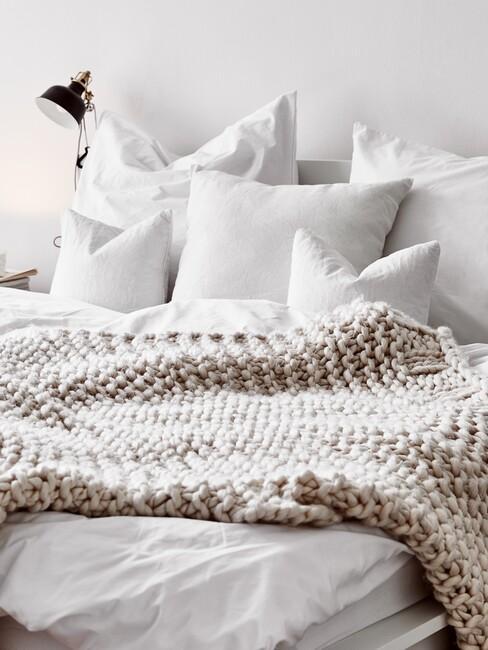 wit bed met beige plaid en zwarte lamp