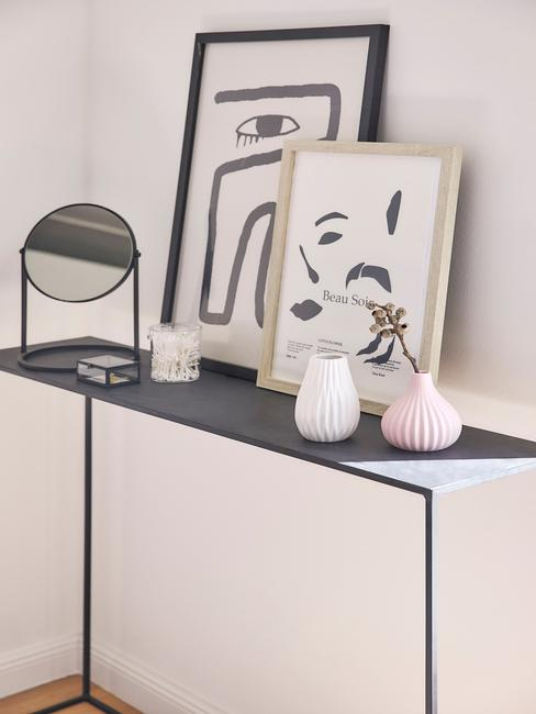 zwarte tafel met fotolijsten en zwarte spiegel