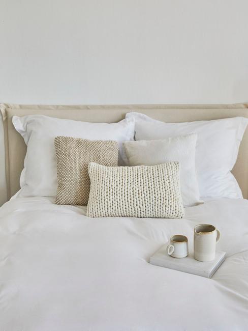 beige bed met wit dekbed en mokken