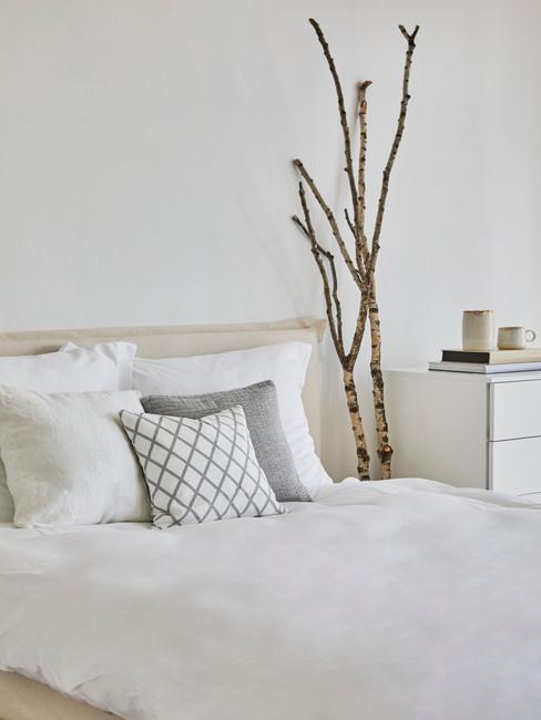 beige bed met een tak en wit dekbed