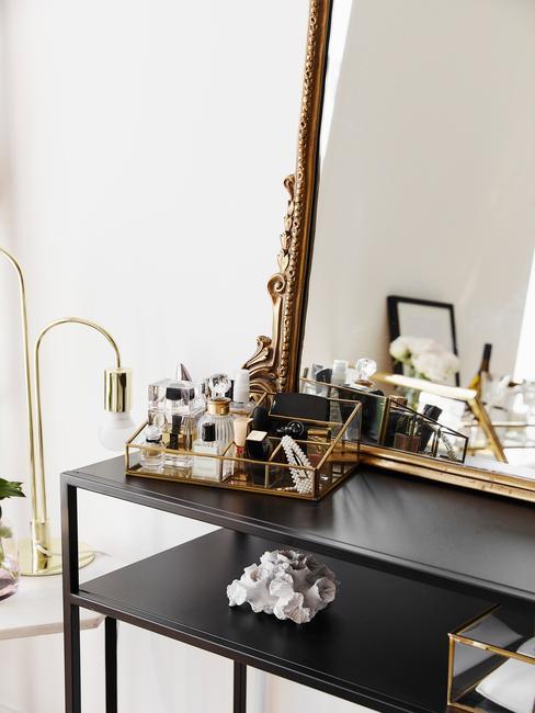 zwarte wandkast met een gouden spiegel