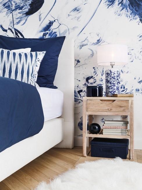 wit bed met blauw behang en blauw dekbed