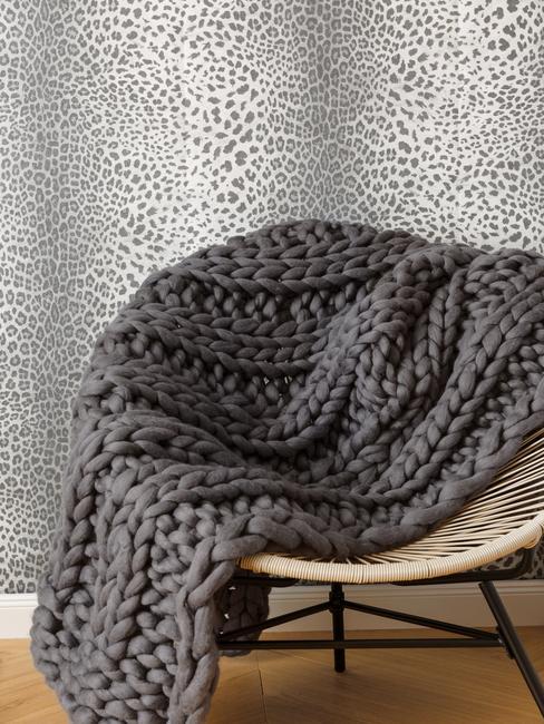 rieten stoel met grijze deken voor panter behang