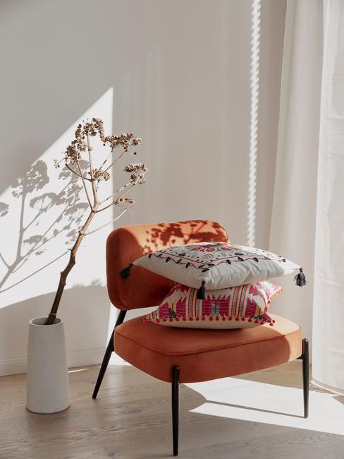 rode stoel met gekleureden kussens en tak in een witte vaas