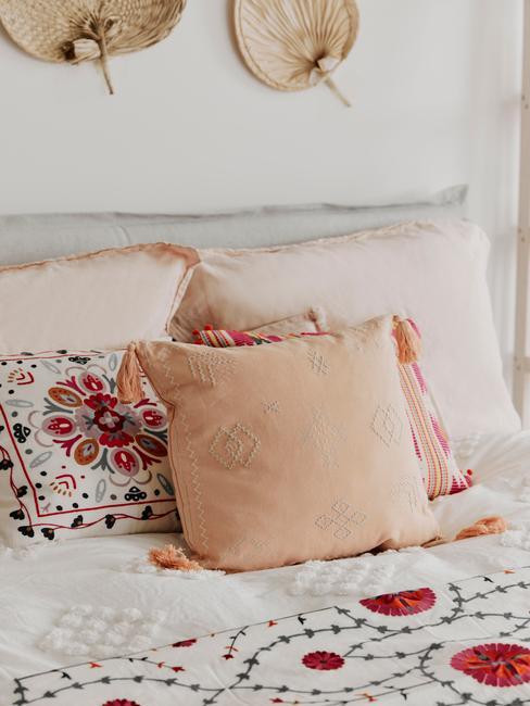 grijs bed met vrolijke kussens met oranje patroon