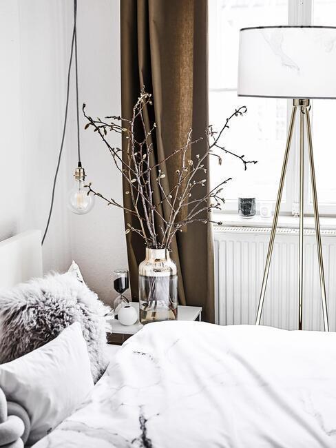witte slaapkamer met witte lamp met gouden poten