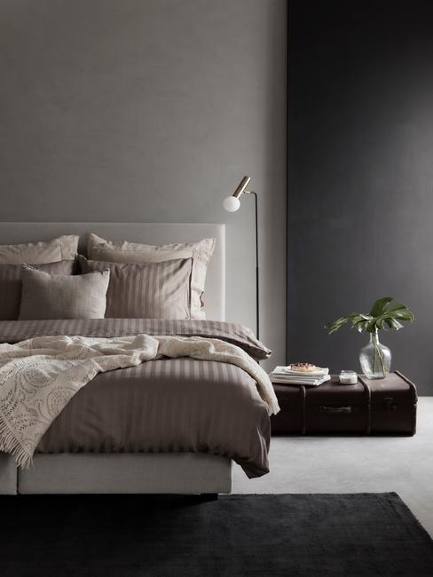 licht bed met donker dekbed en zwarte lamp