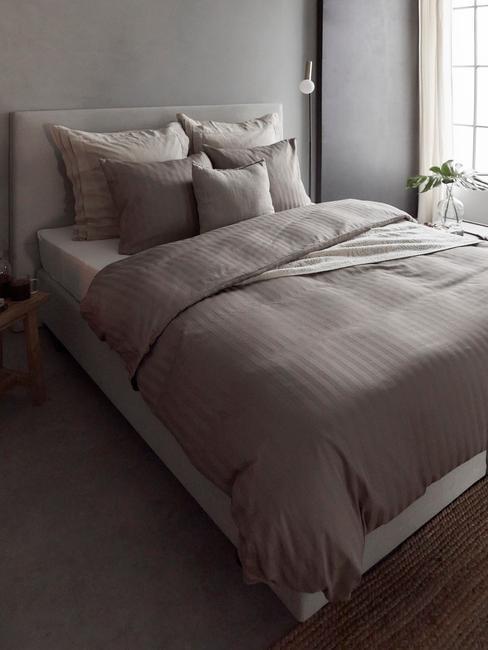 donkere slaapkamer met antreciet dekbed en zwarte lampen