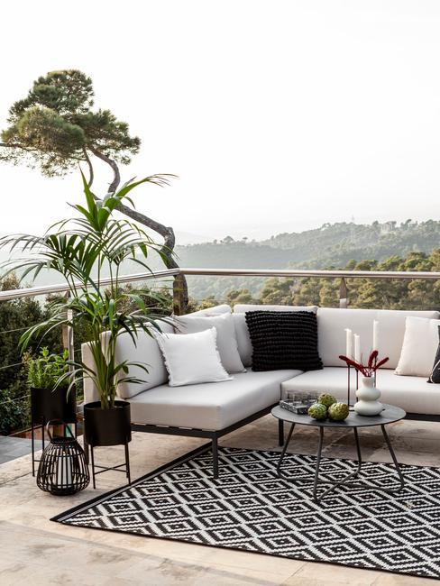 grijze tuinbank met zwarte en witte kussens en zwart met wit buitenkleed