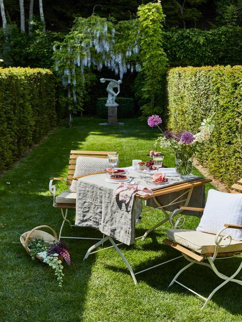 houten tafel en stoelen met witte kussens en wit tafelkleed