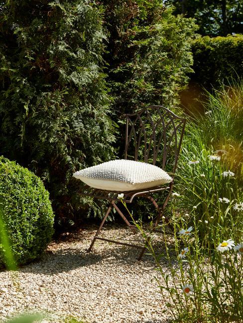 stoel met wit kussen in groene tuin