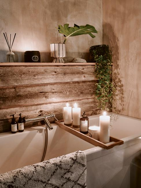 houten badkaer met wit bad en witte kaarsen
