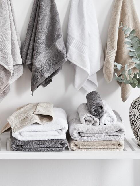 wit bankje met witte en grijze handdoeken