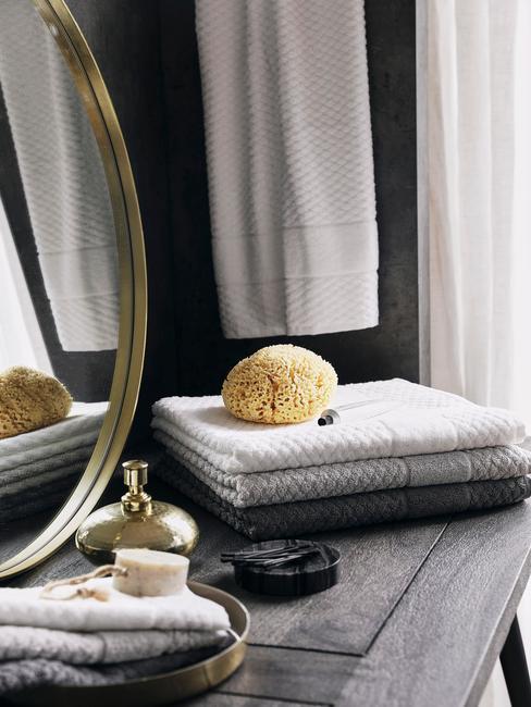 ronde gouden spiegel op donker houten tafel
