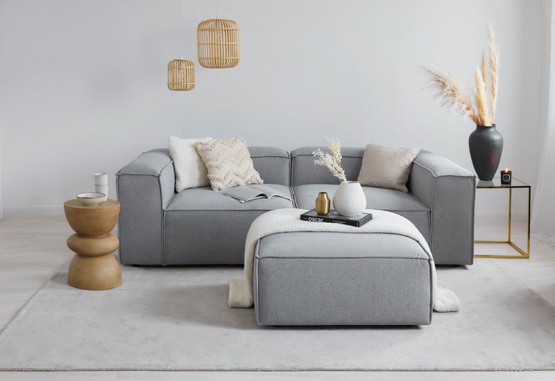 Grijze lennon sofa met ronde bijzettafel en rotan hanglampen