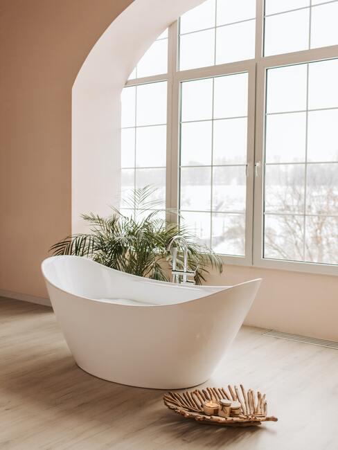 wit ligbad voor groot raam op houten vloer