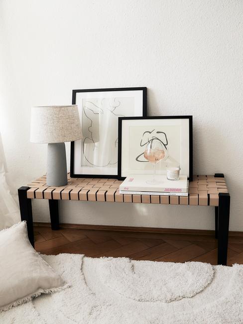 Houten zitbank met leren webbing gecombineerd met lamp, schilderijen met line art en andere decoratieve items