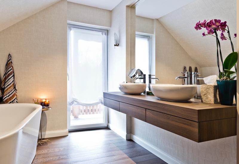 licht grijze tegels met houten meubel en ronde witte kommen