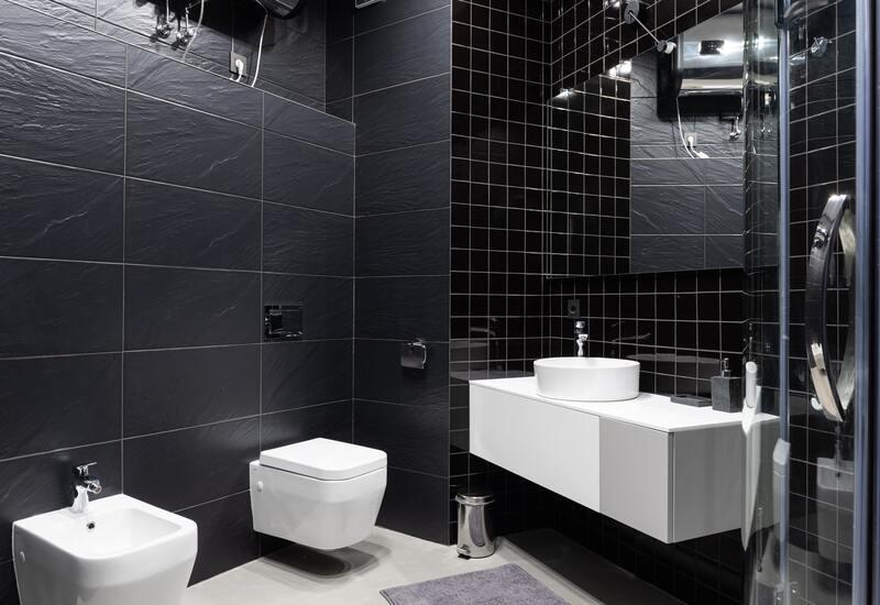 zwarte tegels en witte badkamer meubels