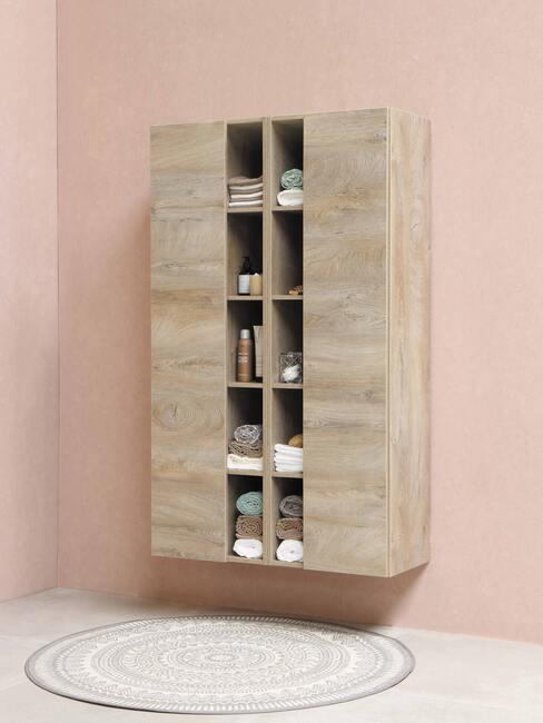 houten kast met kleed en roze muur