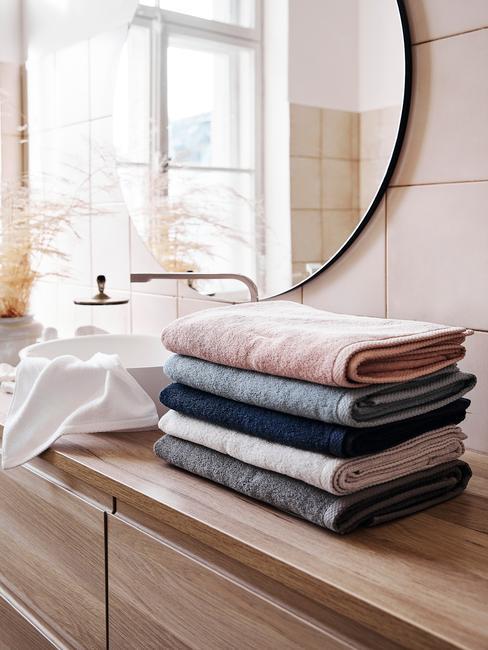 houten meubel met ronde spiegel en gekleurde handdoeken