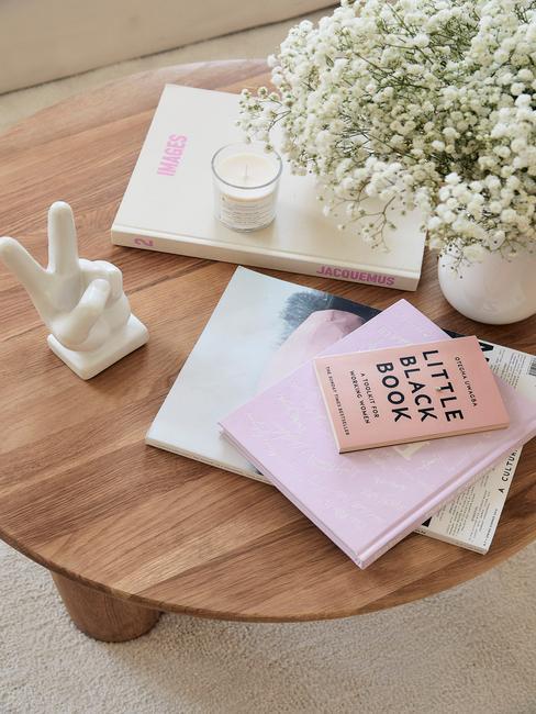 Houten salontafel met boeken, vaas met bloemen en beeldje