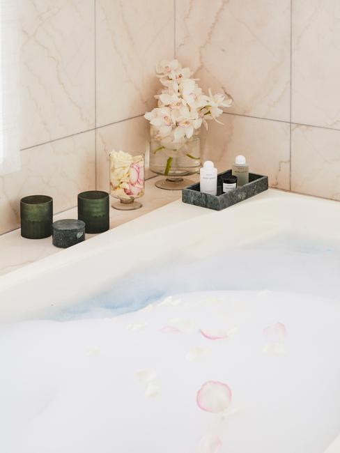 witte tegels met vol bad en kaarsen