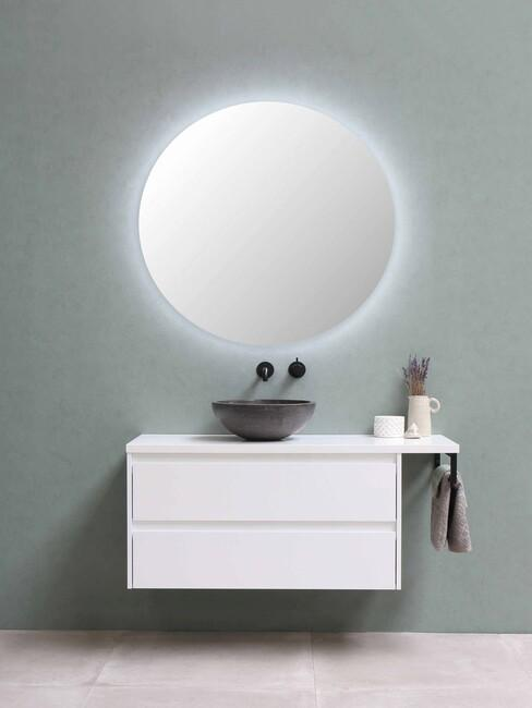 ronde spiegel groene muur en witte kast