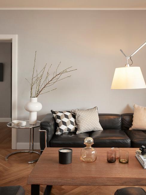 Zwarte leren bank in huiskamer met artemide lamp