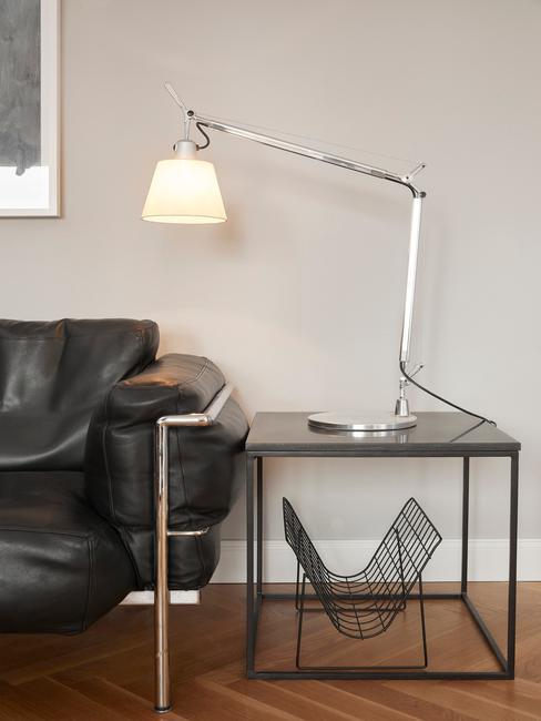 zwarte leren bank met metalen bijzettafel en artemide lamp