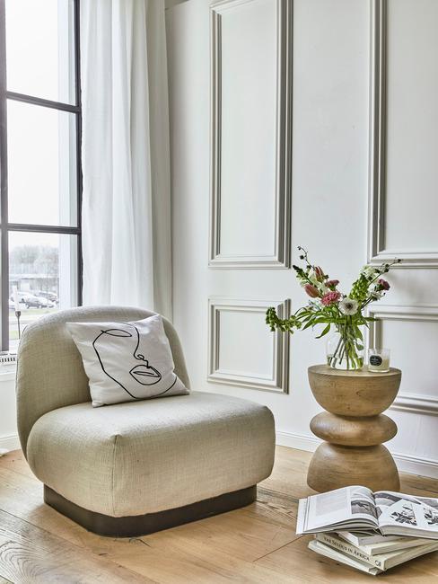 Grote beige lounge stoel naast houten ronde bijzettafel