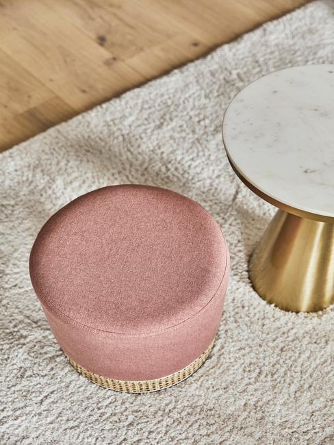 rotan roze poef naast chique marmeren bijzettafel