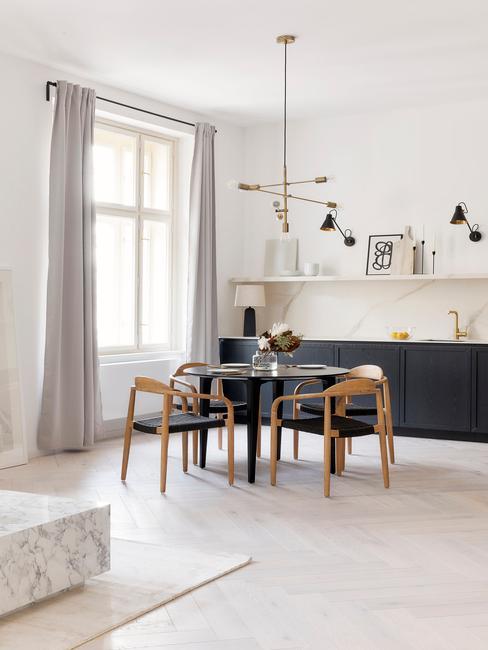woonkamer met ronde eettafel en houten stoelen
