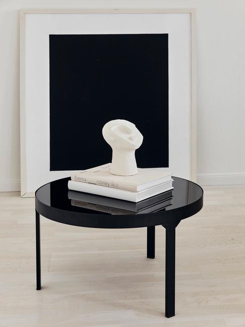 zwarte tafel met witte boeken en beeld