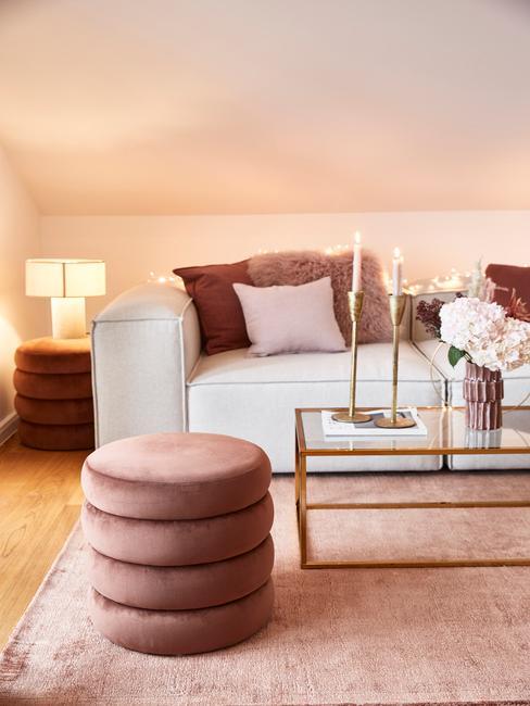grijze bank met roze kussens en gouden tafel