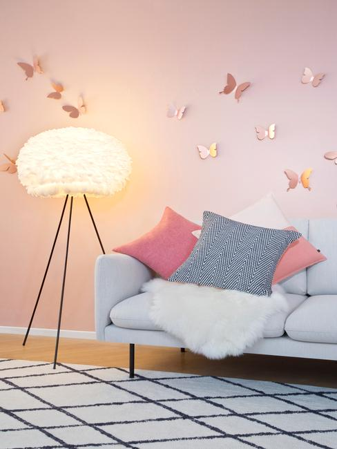 roze muur met grijze bank en gouden vlinder stickers