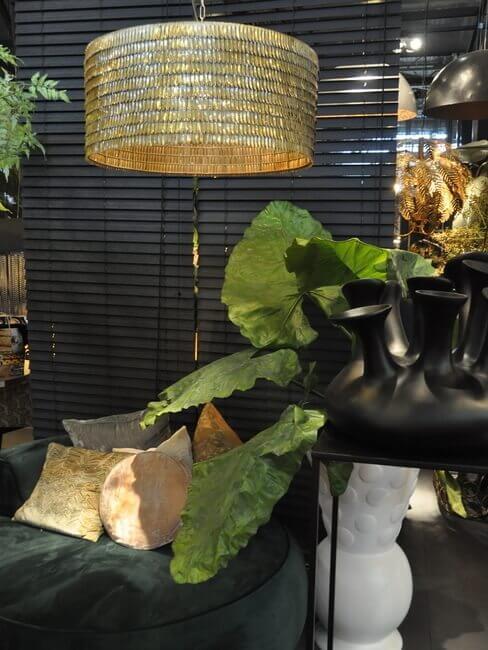 Woonkamerhoek met goude kroonluchter, zwarte vazen en grote plant