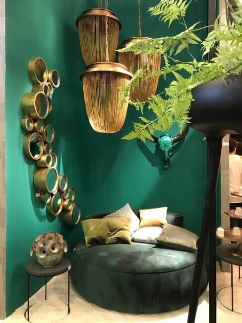 Woonkamerhoek met groene muur en goude accenten