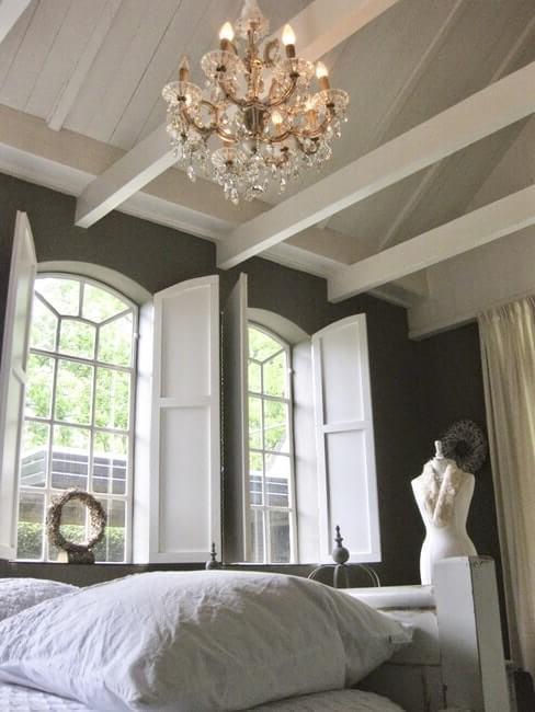 Landelijke huisstijl slaapkamer met kroonluchter en grote ramen