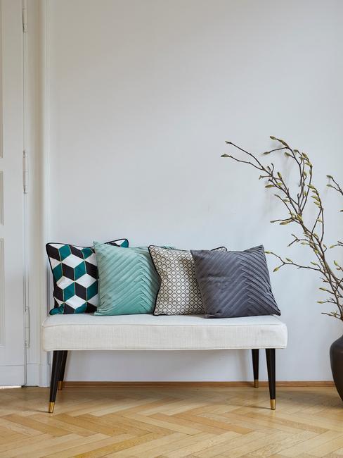 grijs bankje met gekleurde kussens en houten vissengraat vloer