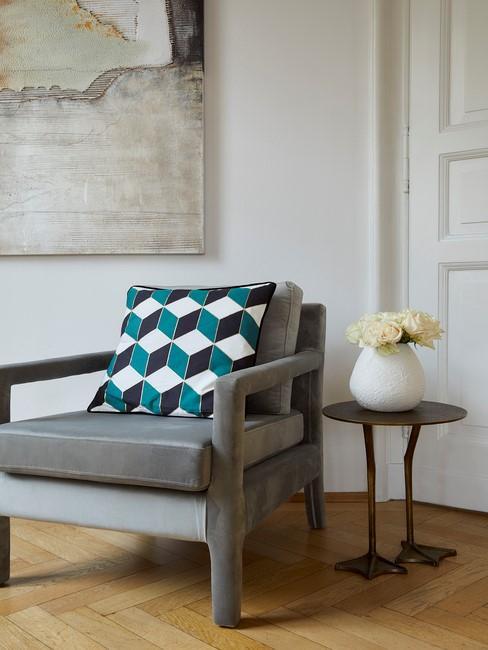 grijze stoel met blauw kussen en houten vloer
