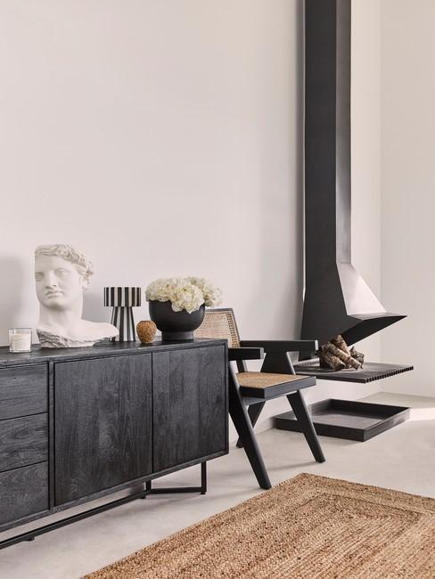 zwarte kast zwarte stoel en zwarte openhaard en bruin kleed