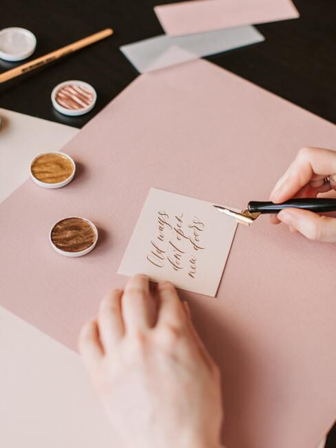 roze bureau met wit briefje met zwarte inktpen