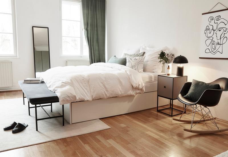 wit bed met witte deken en zwart bankje